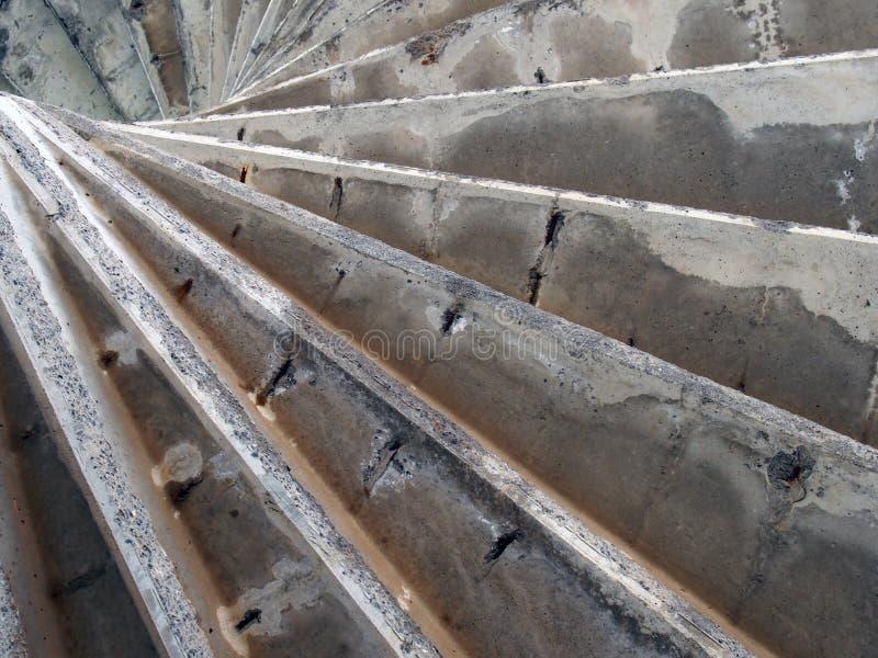 Onderaan oude geërodeerde versleten concrete spiraalvormige treden die een geometrische samenvatting vormen stock afbeeldingen