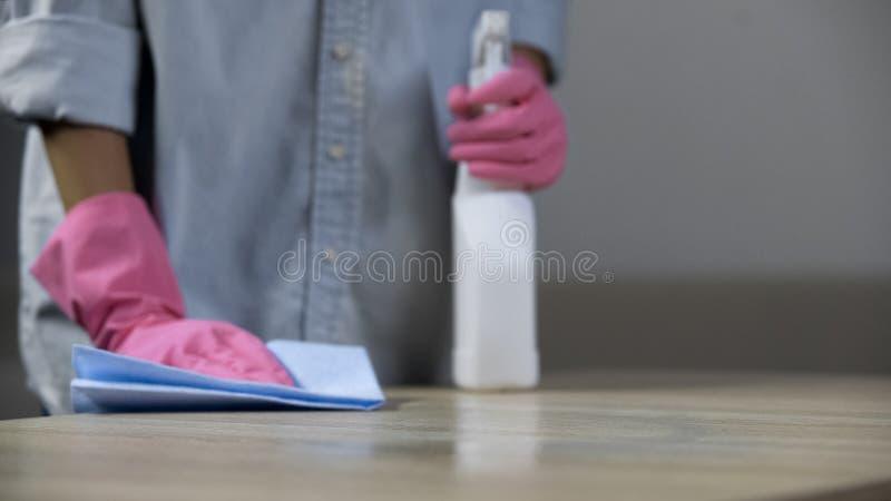 Onderbetaalde arbeider die een vuil bureau in schoolcafetaria schoonmaken, low-paid beroep stock afbeeldingen