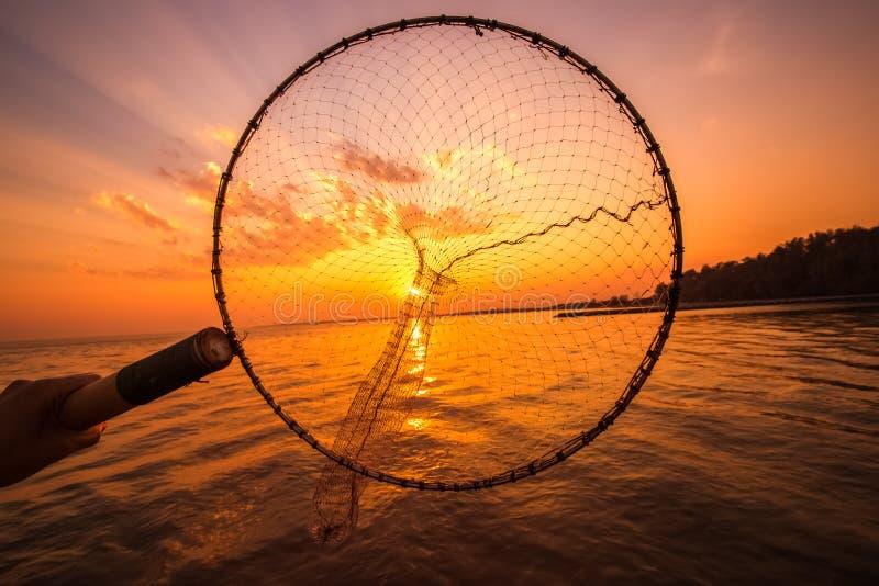Onderdompeling netto in boot die op zonsopgang, zonsondergangwater vissen royalty-vrije stock fotografie