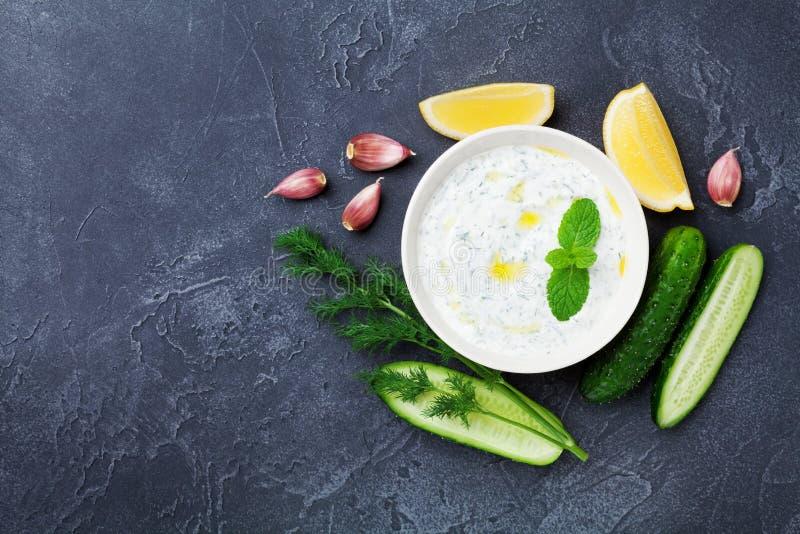 Onderdompeling of saustzatziki van Griekse yoghurt met ingrediëntenkomkommer, dille, citroen, munt en knoflook op zwarte de boven royalty-vrije stock afbeelding