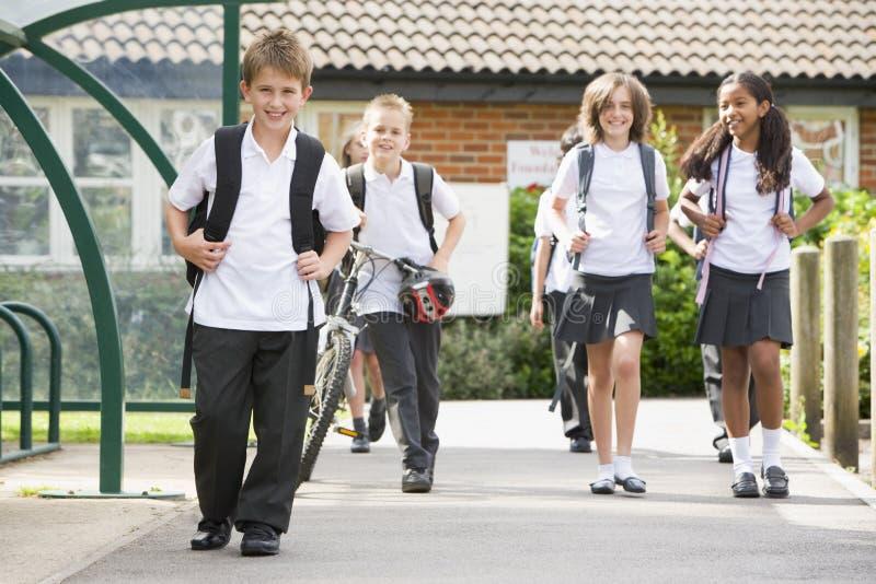 Ondergeschikte schoolkinderen die school verlaten royalty-vrije stock afbeeldingen