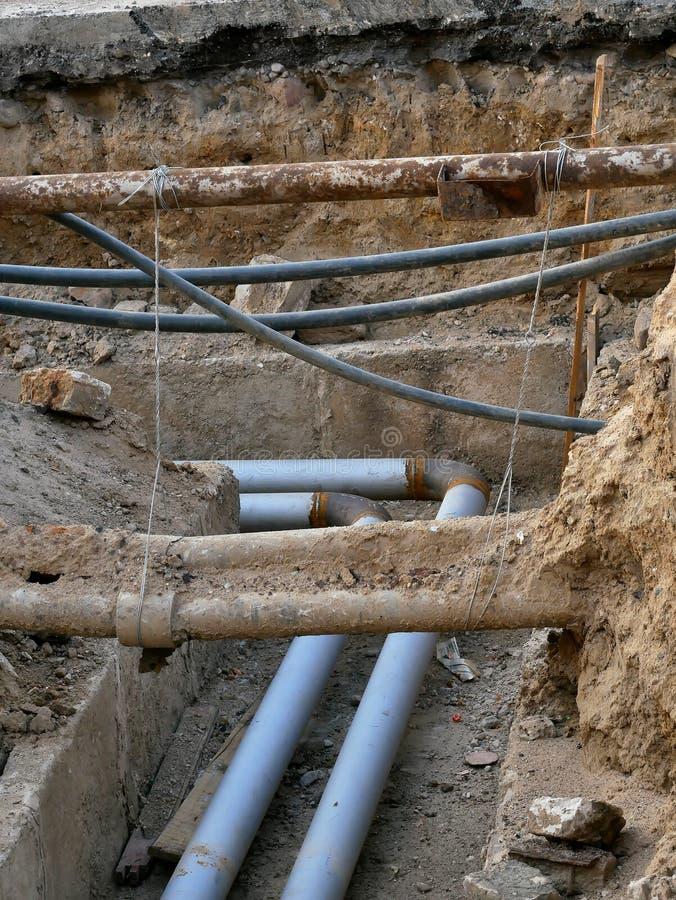 Ondergrondse nut, opgegraven pijpen in de grond stock foto