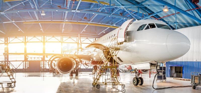 Onderhoud en reparatie van vliegtuigen in de luchtvaarthangaar van de luchthaven, mening van een breed panorama stock afbeelding