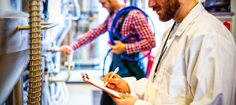 Onderhoudsarbeiders die brouwerijmachine onderzoeken royalty-vrije stock foto