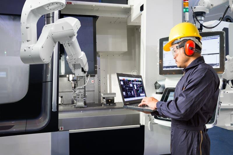 Onderhoudsingenieur die laptop de automatische robotachtige hand van de computercontrole met CNC machine in slimme fabriek, Indus royalty-vrije stock afbeelding