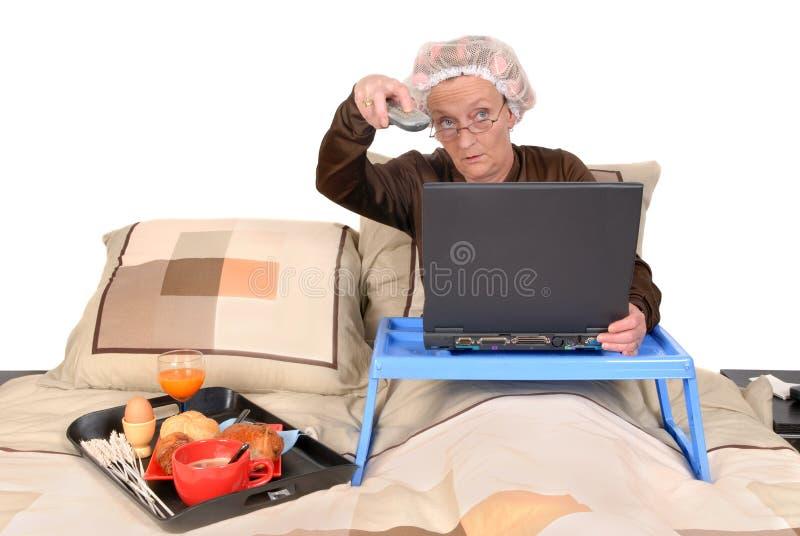 Onderneemster in bed, het werken stock afbeeldingen