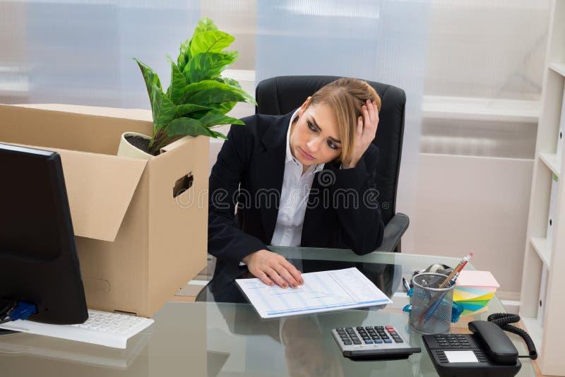 Onderneemster bij bureau met bezittingen in doos royalty-vrije stock foto