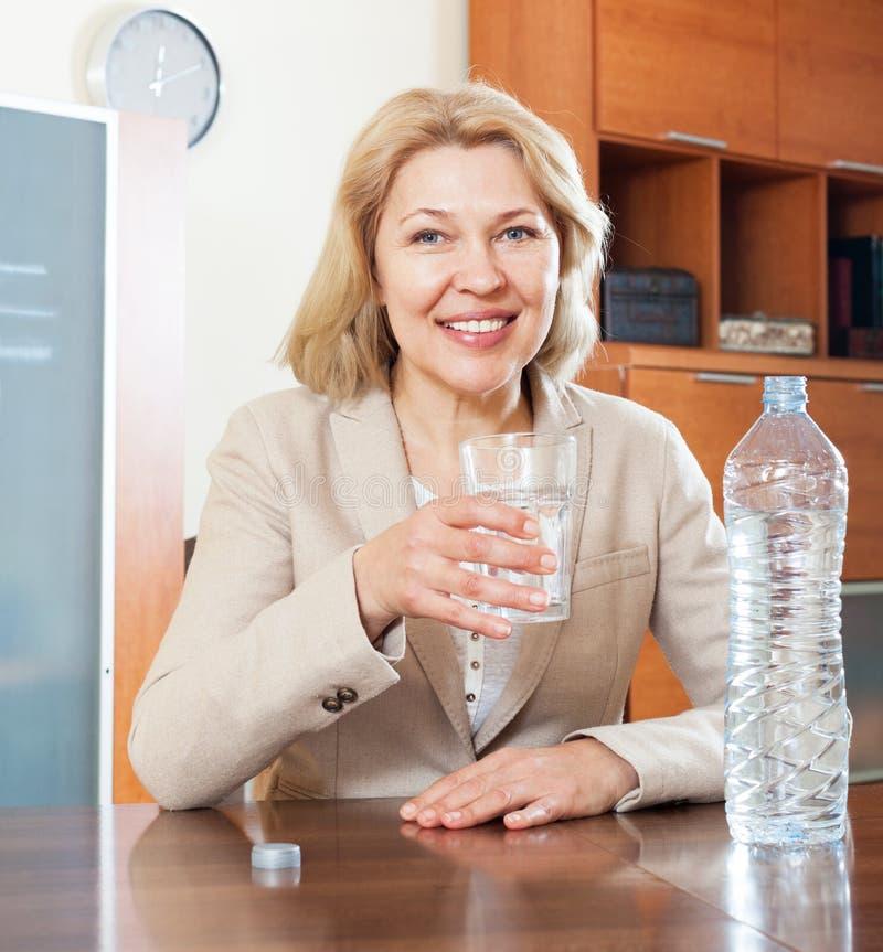 Onderneemster bij bureau met glas water royalty-vrije stock fotografie