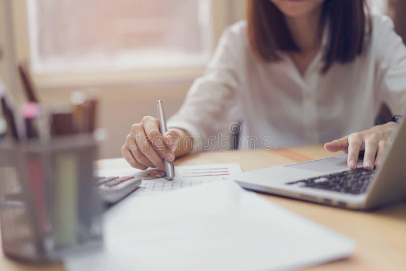 Onderneemster in bureau en gebruikscomputer en calculator om financiële boekhouding uit te voeren stock foto's