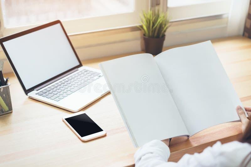 Onderneemster in bureau in toevallig overhemd De gebruikscomputer voor grafische ontwerper en houdt een blanco paginaboek stock afbeelding