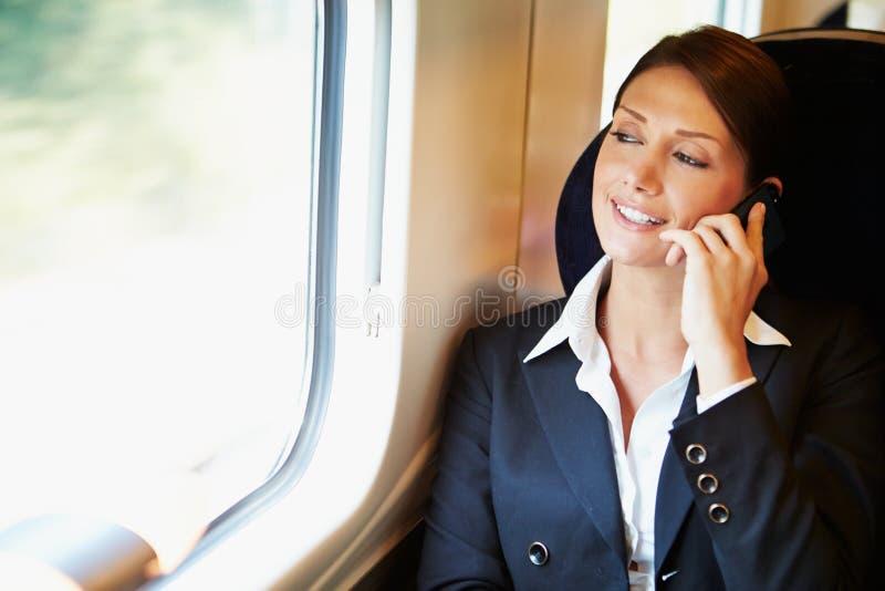 Onderneemster Commuting To Work op Trein die Mobiele Telefoon met behulp van royalty-vrije stock foto's