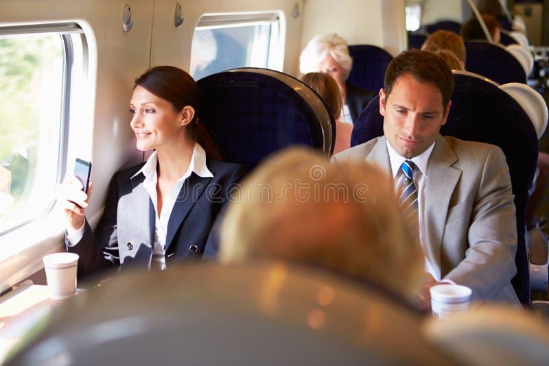 Onderneemster Commuting To Work op Trein die Mobiele Telefoon met behulp van royalty-vrije stock afbeeldingen
