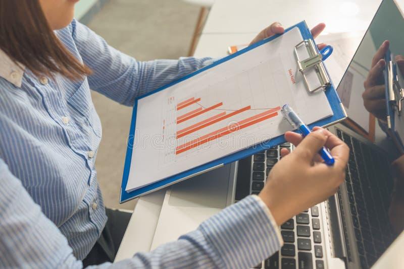 Onderneemster in de blauwe financiële verslagen van de overhemdslezing in het bureau stock foto's