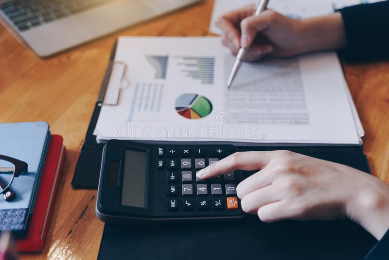Onderneemster die aan calculator werken om bedrijfsgegevensfinancieel verslag op houten lijst te berekenen stock foto's