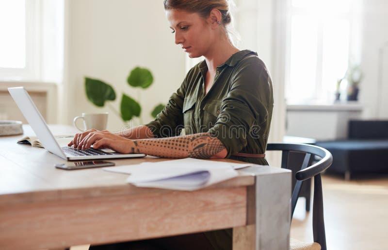 Onderneemster die aan laptop thuis bureau werken stock afbeeldingen