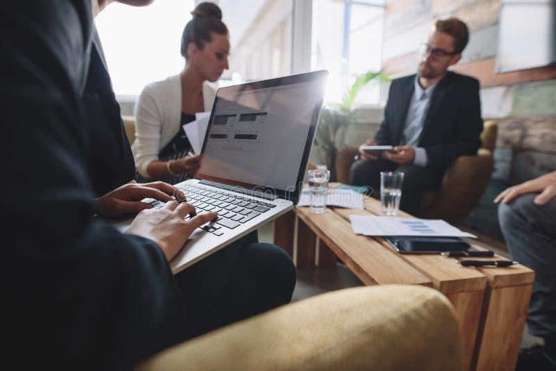 Onderneemster die aan laptop tijdens vergadering werken royalty-vrije stock foto's