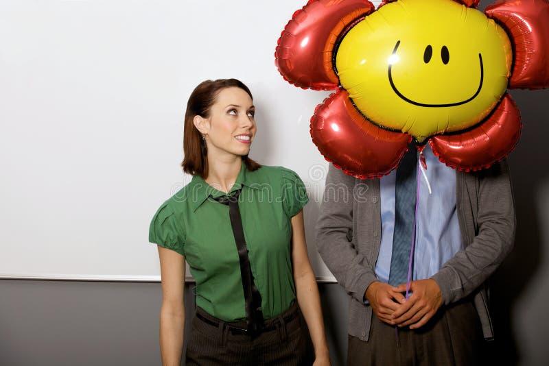 Onderneemster die ballon over man gezicht bekijken royalty-vrije stock fotografie