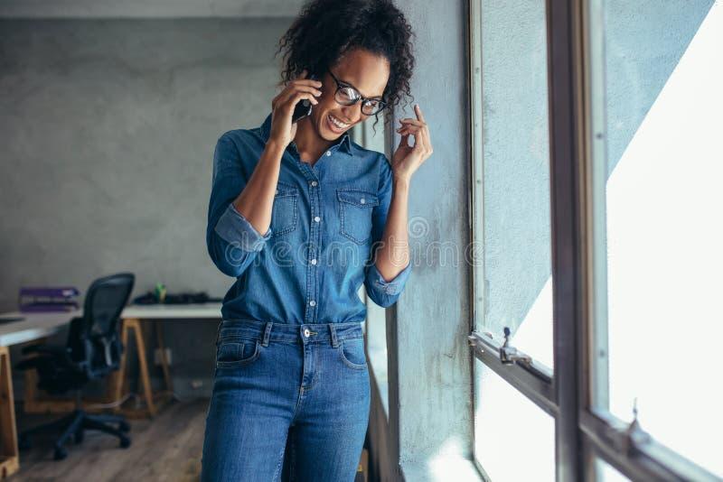 Onderneemster die bij mobiele telefoon en het glimlachen spreken stock afbeelding