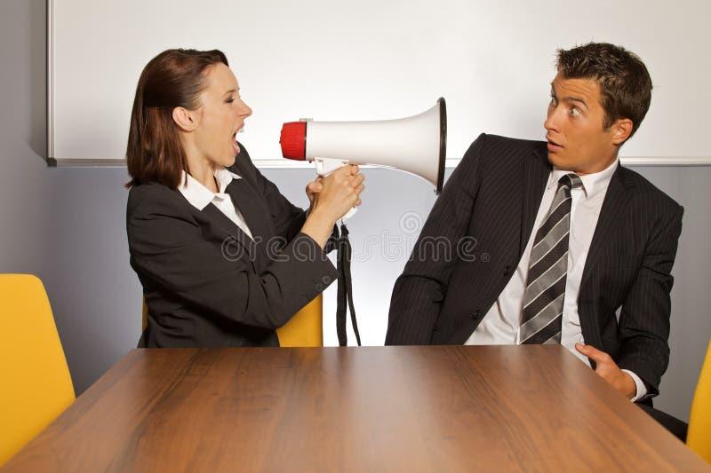 Onderneemster die bij zakenman door megafoon schreeuwen stock afbeelding