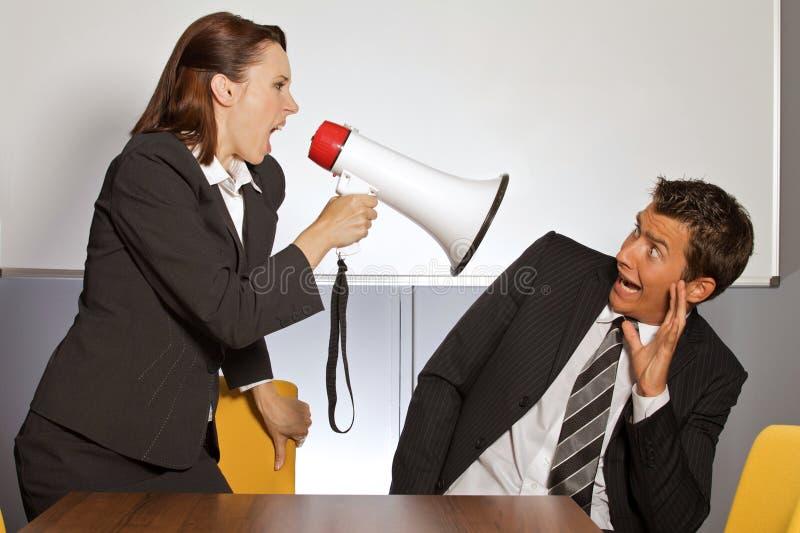 Onderneemster die bij zakenman door megafoon schreeuwen stock fotografie