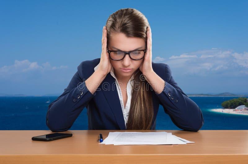 Onderneemster die in bureau, vakantie werken, bekijkend documenten, die denken, stock fotografie
