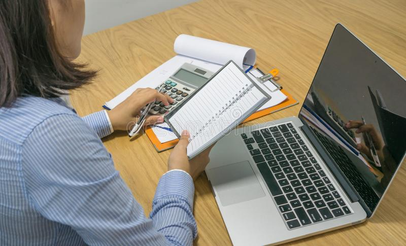 Onderneemster die calculator gebruiken om financieel aantal op document te controleren stock foto's