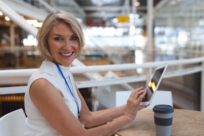 Onderneemster die camera bekijken terwijl het werken aan digitale tablet bij lijst in een modern bureau stock fotografie