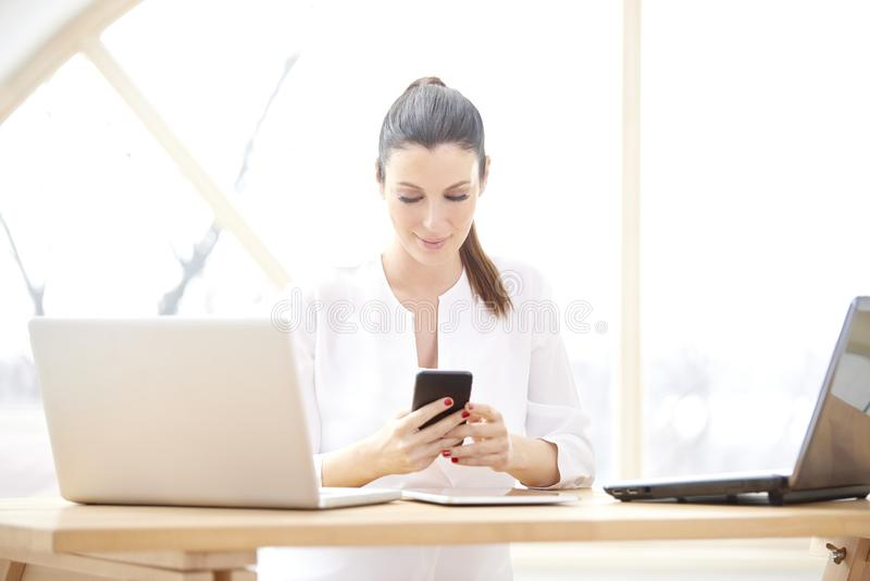 Onderneemster die celtelefoon en laptops met behulp van royalty-vrije stock fotografie