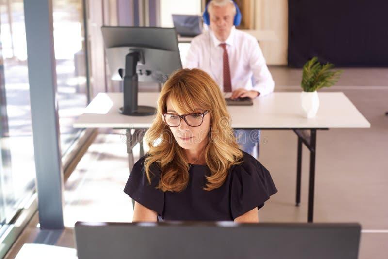 Onderneemster die comptur in het bureau werken stock afbeelding