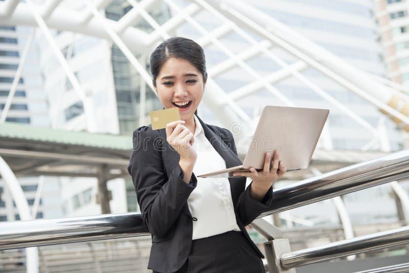 Onderneemster die computer en creditcard voor Internet-bank gebruiken stock fotografie