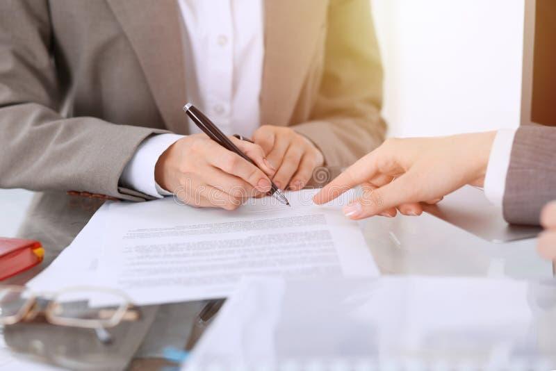 Onderneemster die contractdocumenten ondertekenen Groep bedrijfsmensen bij vergadering of onderhandeling, close-up stock afbeelding