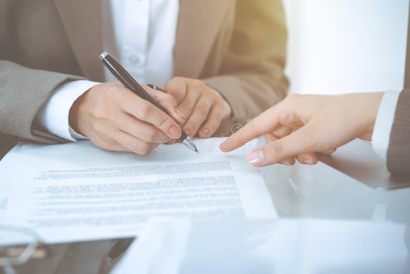 Onderneemster die contractdocumenten ondertekenen Groep bedrijfsmensen bij vergadering of onderhandeling, close-up stock afbeeldingen