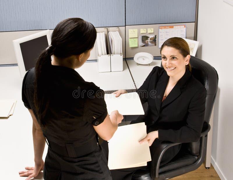 Onderneemster die de omslag van het medewerkerdossier overhandigt stock afbeeldingen