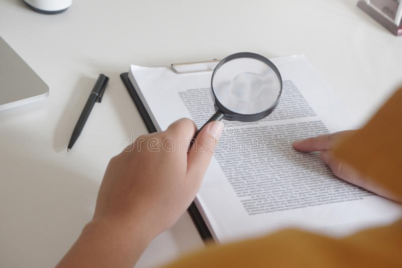 Onderneemster die door een vergrootglas aan documentennota kijken in het bureau royalty-vrije stock afbeelding