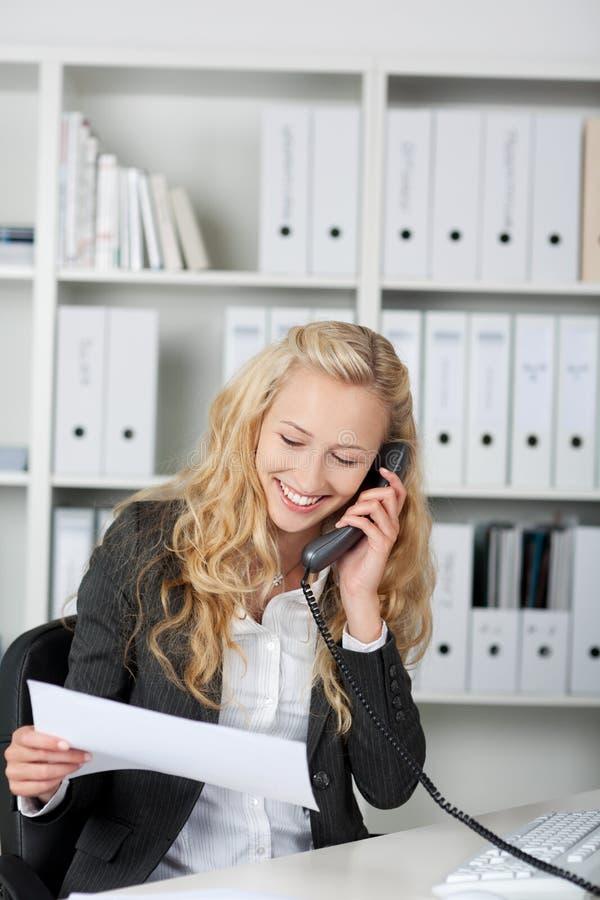 Onderneemster die een fax leest en op telefoon spreekt stock fotografie