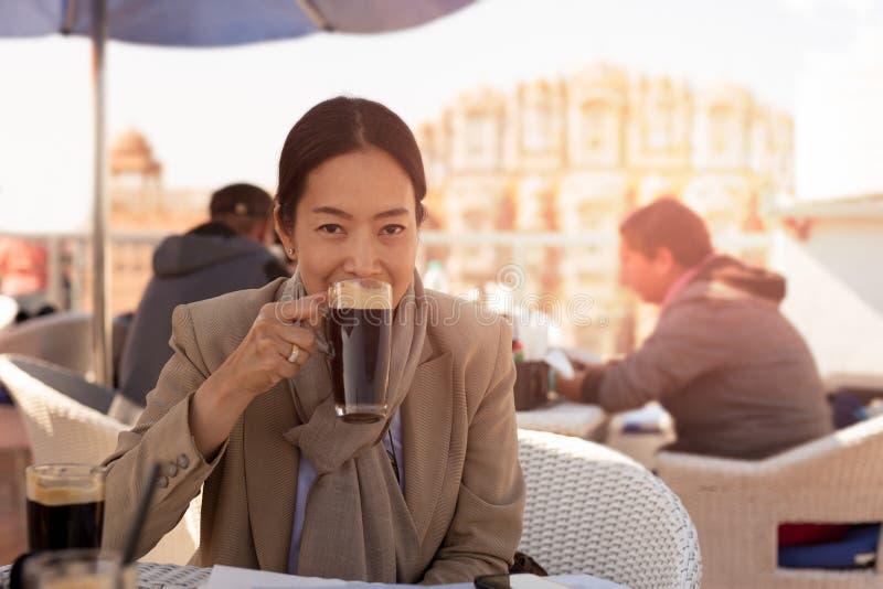 Onderneemster die een kop van koffie openluchtkoffie hebben die camera bekijken stock afbeeldingen