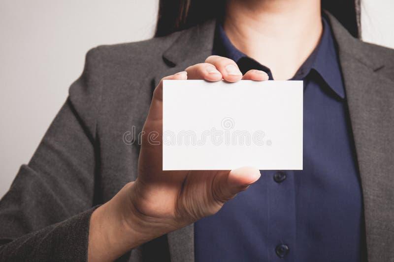 Onderneemster die en een leeg adreskaartje toont overhandigt stock fotografie