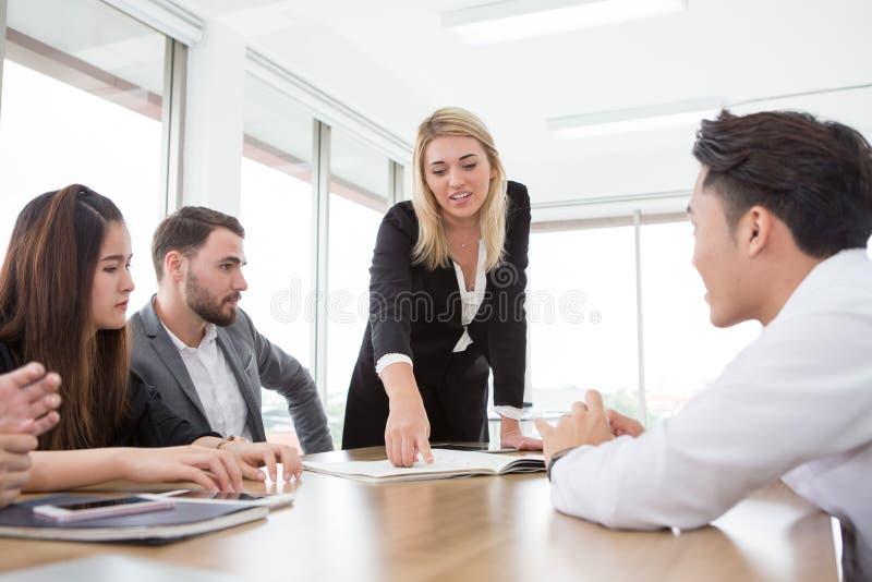 onderneemster die en op het grafiek of documentdocument in vergaderzaal voorstellen richten Groep jonge bedrijfsmensen royalty-vrije stock foto