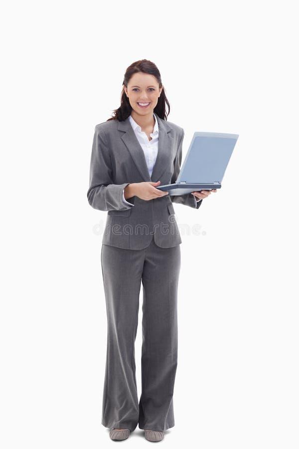 Onderneemster die gelukkig met laptop kijkt stock foto