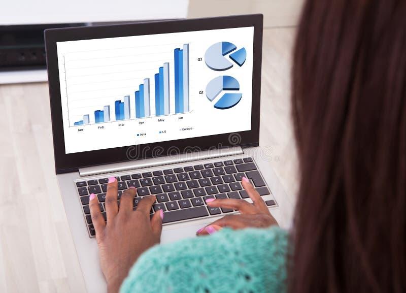 Onderneemster die grafieken op laptop thuis analyseren royalty-vrije stock afbeeldingen
