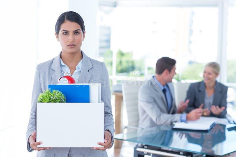 Onderneemster die haar bezittingen in doos dragen stock foto's