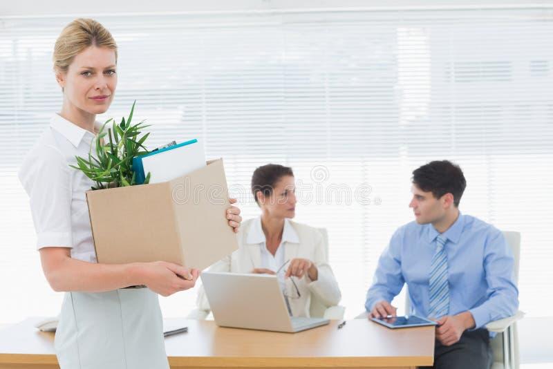 Onderneemster die haar bezittingen met collega's op achtergrond dragen stock afbeeldingen