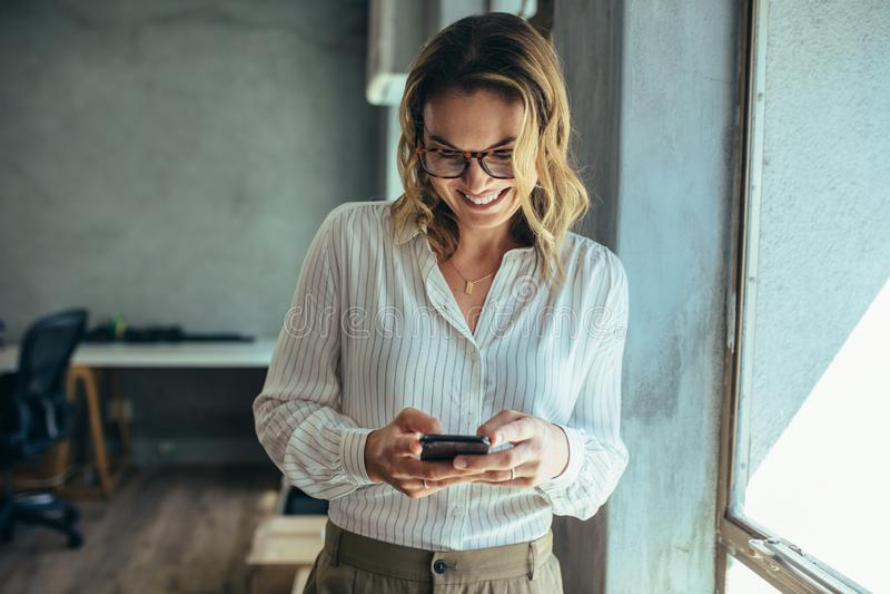 Onderneemster die haar slimme telefoon in bureau met behulp van royalty-vrije stock foto's