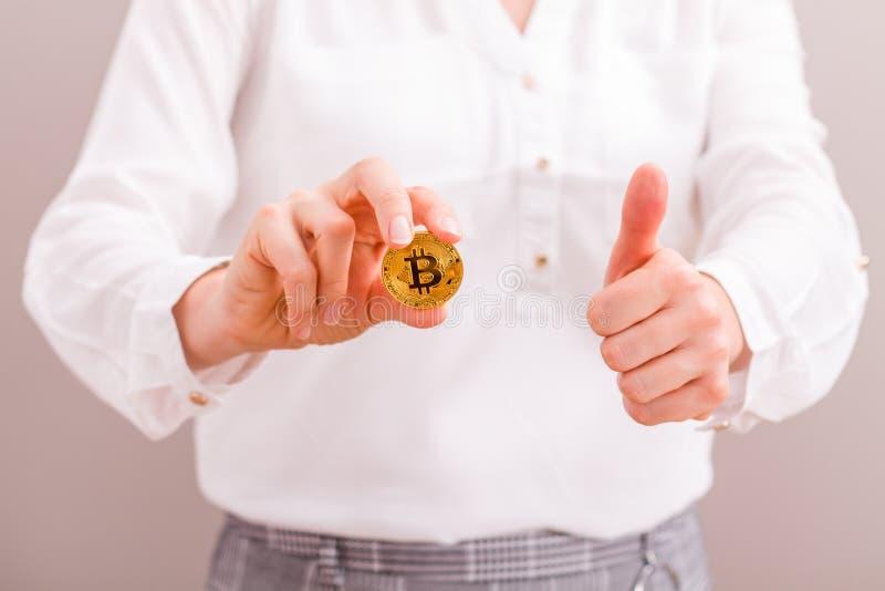 Onderneemster die het bitcoin gouden muntstuk en de duim tegenhouden royalty-vrije stock fotografie