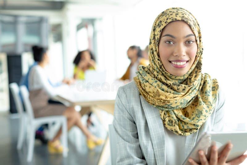 Onderneemster die in hijab met digitale tablet camera bij conferentieruimte bekijken in een modern bureau royalty-vrije stock foto