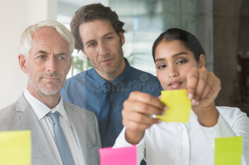 Onderneemster die kleverige nota's plakken royalty-vrije stock afbeelding