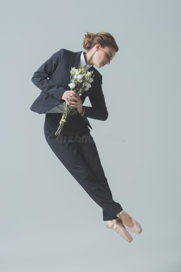 onderneemster die in kostuum en balletschoenen met boeket van bloemen springen royalty-vrije stock fotografie