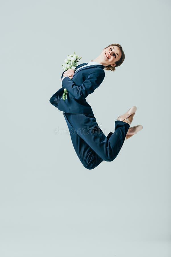 onderneemster die in kostuum en balletschoenen met boeket van bloemen springen stock fotografie