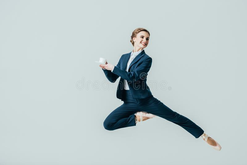 onderneemster die in kostuum en balletschoenen met kop van koffie springen royalty-vrije stock foto's