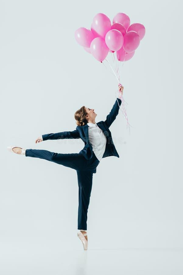 onderneemster die in kostuum en balletschoenen roze ballons houden royalty-vrije stock afbeelding